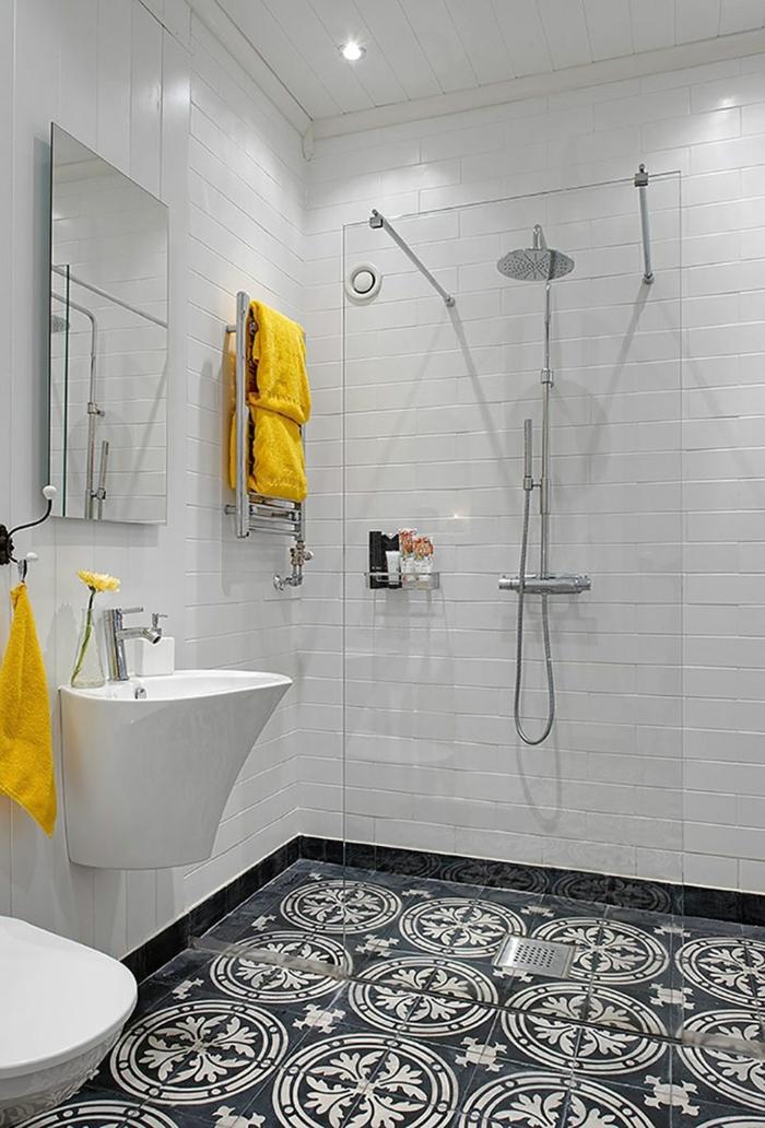 baño en blanco y negro, accesorios en amarillo, duchas de obra, mampara de vidrio, baldosas con patron floral, luces empotradas en el techo