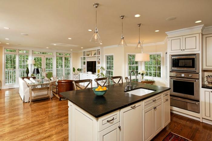 salon cocina con luces empotrados, espacio decorado en blanco y color champán con grande marra con alacenas y suelo de parquet