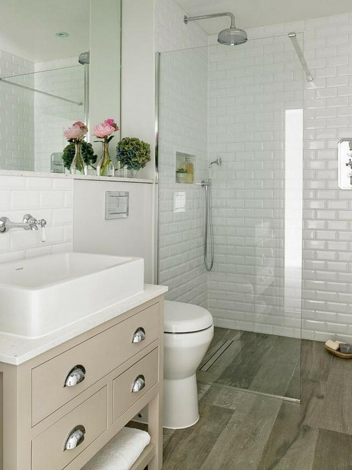 baños pequeños con ducha, combinación blanco con color crema, espejo grande, decoracion con flores, pared de ladrillo visto esmaltado, ducha con mampara de vidrio, suelo con tarima