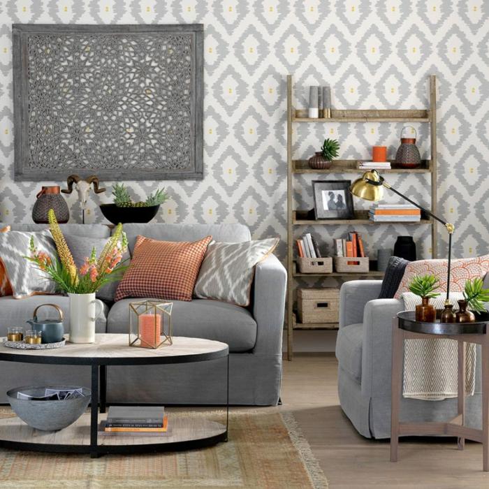 papel pintado en rombos grises, habitacion gris y blanca, mesita redonda de metal y madera, cojines en color naranja, flores, etsntería simple rústica