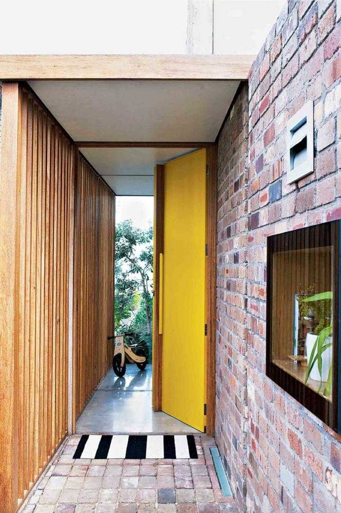 recibidor moderno con paredes de ladrillo, puerta pintada en amarillo y estantería con plantas verdes