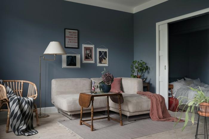 decoracion nordica salon, espacio pequeño, sofá beige con cojines y cubierta en rosado, paredes gris con cuadros, mesa moderna de madera, tapete, puerta deslizante y dormitorio