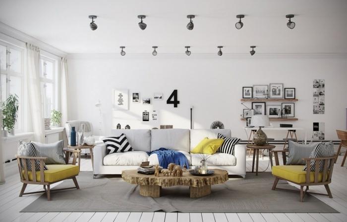 sala de estar grande con mucha luz natural, sofá blanca, cojines amarillos y rayados en blanco y negro, sillones de madera, tarima en el suelo, alfombra gris, decoracion con cuadros, mesa de madera rustica, dormitorio nordico