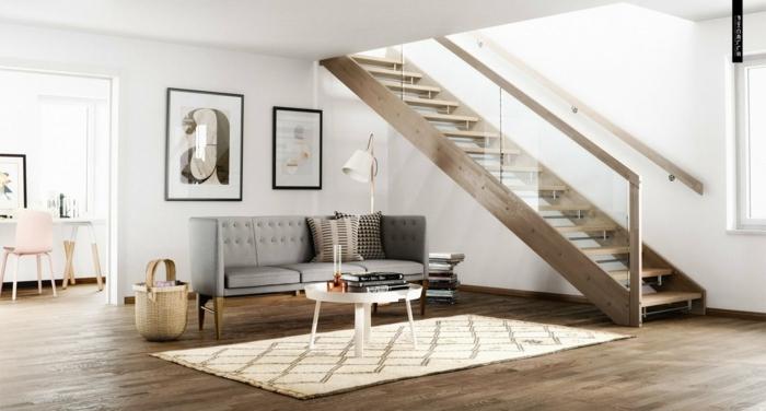 salon bajo escalera con barandilla de vidrio, casas nordicas, suelo con tarima, sofá gris en capitoné, alfombra en rombos, mesita baja redonda