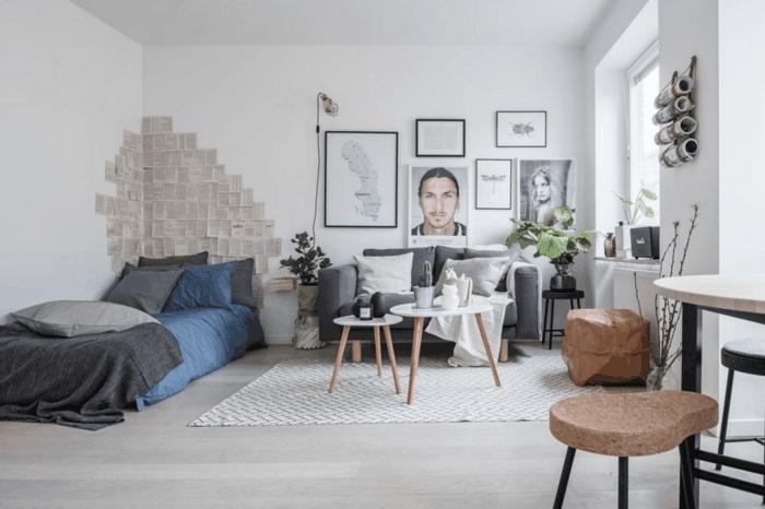 dormitorio nordico, habitación con cama y sofá, pared decorada con páginas de libros, cuadros y retratos, mesitas de café blancas con patas de madera, alfombra, suelo laminado