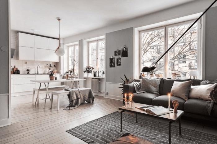 decoracion en blanco y gris, estilo nórdico, salón comedor, mesa con bancos, sofá gris oscuro con cojines, mesa de café rectangular con velas, tapete, ventanas grandes sin cortinas