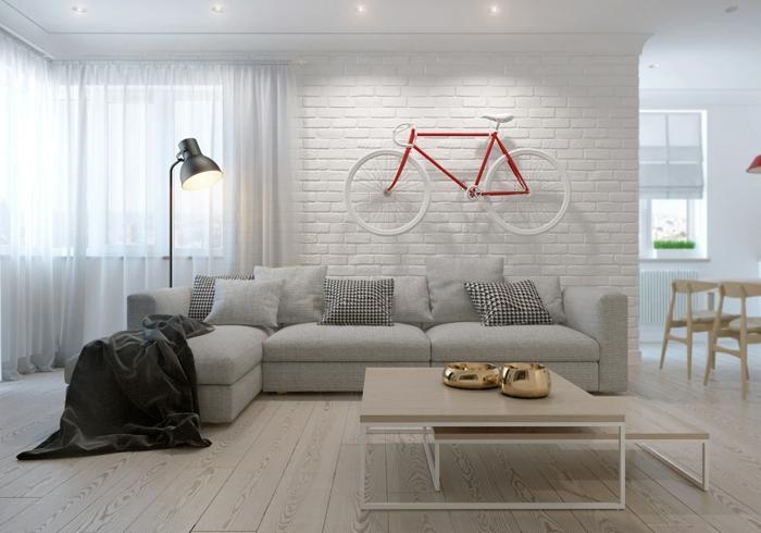 estilo nórdico, sala de estar, ladrillo visto pintado blanco, decoración con bicicleta, sofá gris con cojines, mesa con dos niveles de madera, suelo con tarima, cortinas ligeras