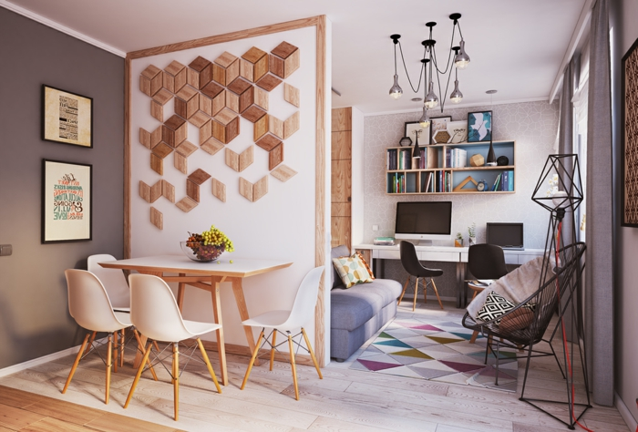 salon comedor pequeño, decoracion nordica salon, pared decorada con pedazos de madera, mesa y sillas de plástico y madera clara, tapete con triángulos, silla acapulco, escritorio y estantería pequeña