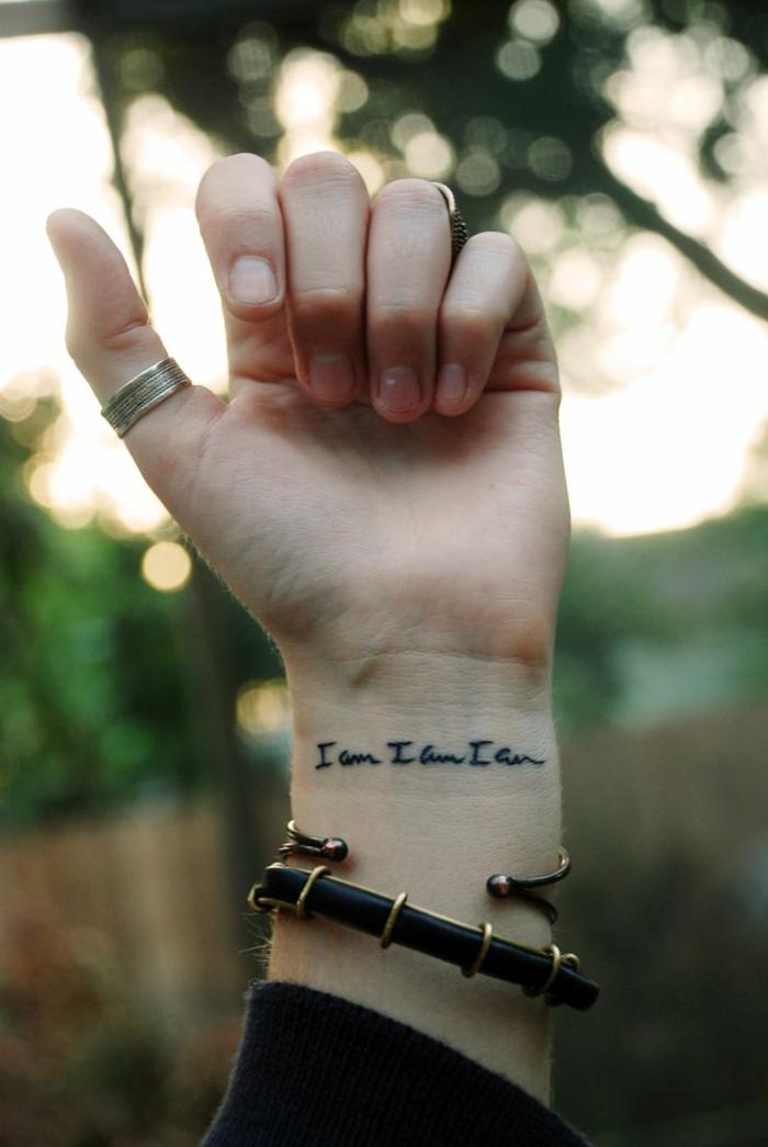 tattoos pequeños, mano con pulsera y anillos, tatuaje en la muñeca con frase en negro cursiva, estilo minimalista