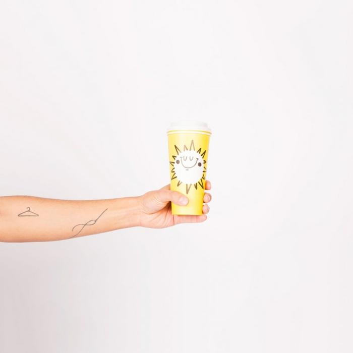 tatuajes minimalistas, mano colgando taza de cafe amarilla con sol, antebrazo tatuado con percha y aguja con hilo