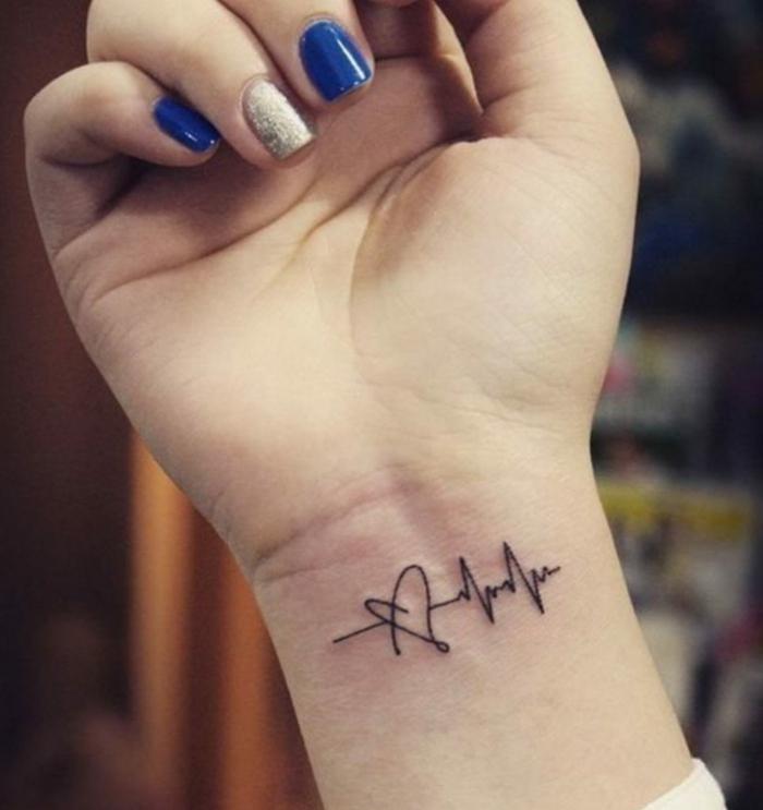 tatuaje con significado, mano de mujer con uñas pintadas, tatuaje negro en la muñeca, frecuancia cardíaca y corazón, tattoo en la muñeca