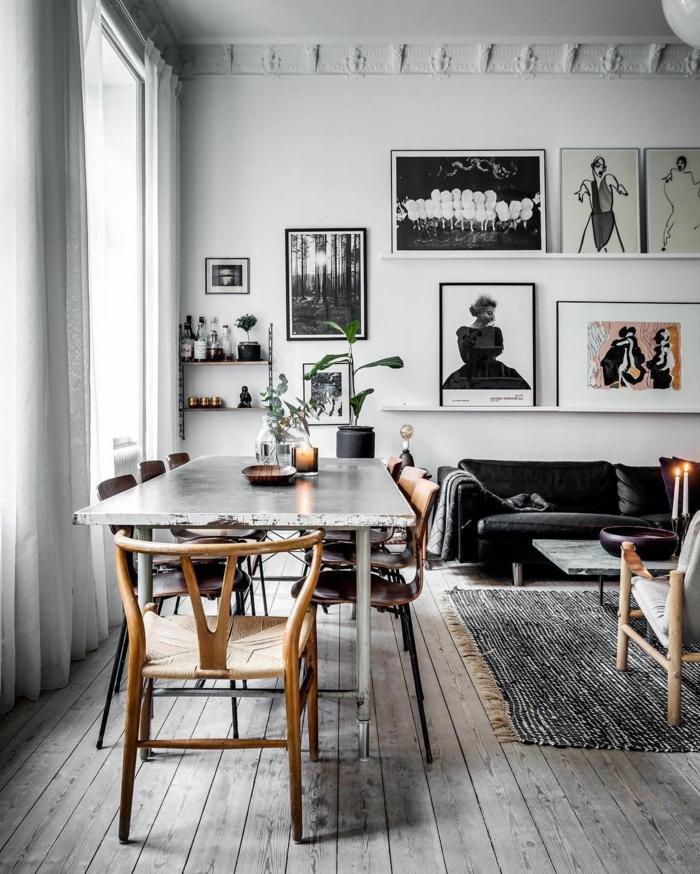 salon comedor en blanco y negro, mesa con sillas desparejas, estilo nordico, pared decorada con obras de arte modernas, sofá en terciopelo negro, velas encendidas, suelo con tarima y tapete