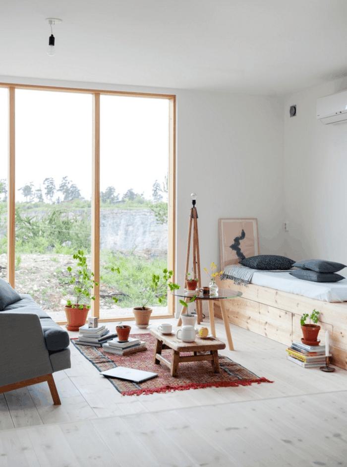 dormitorio nordico, habitación pequeña con ventanal, tapete rojo, mesita redonda de vidrio, sofá gris, plantas verdes