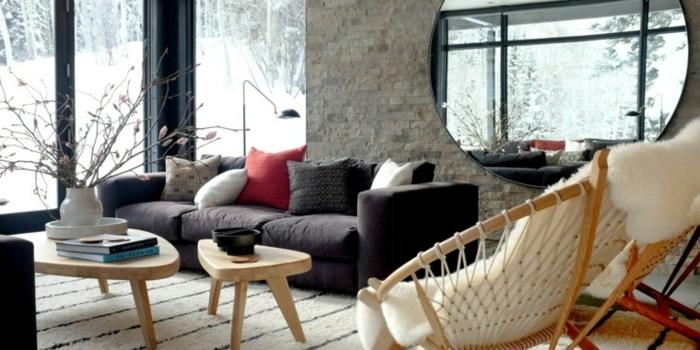 salón acogedor con muebles de estilo moderno, grande espejo oval colgado en la pared, paredes de ladrillo y suelo con parquet