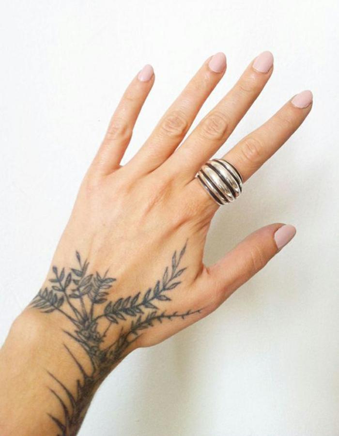 mujer con uñas pintadas en rosado y anillos, tatuaje floral en negro que empieza en la muñeca y sigue en la mano, tatuajes en la muñeca