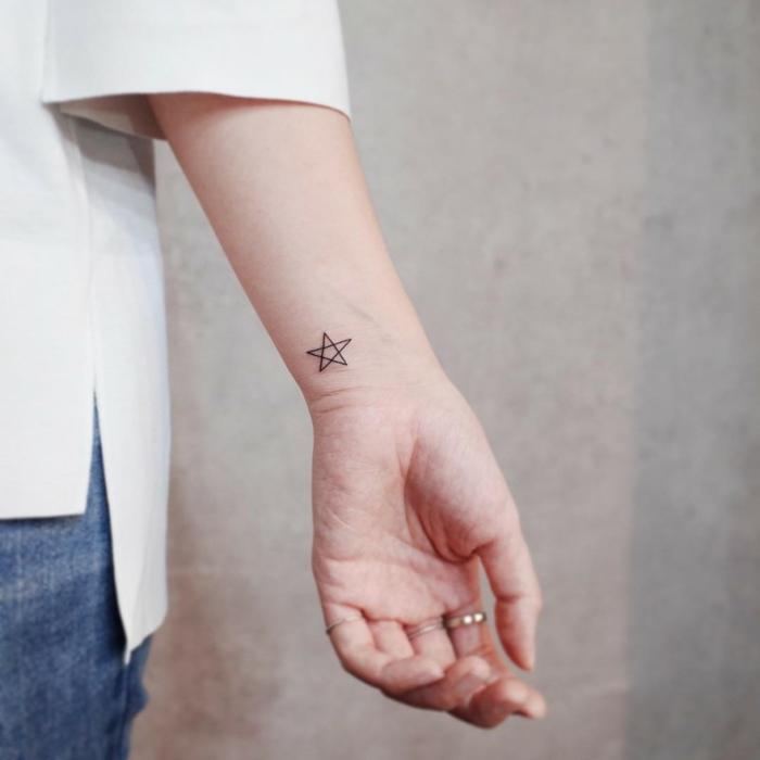 mujer con camisa de mangas tres cuartos y anillos, tatuaje minimalista en la muñeca, estrella de cinco puntos, tatuajes pequeños para mujeres originales