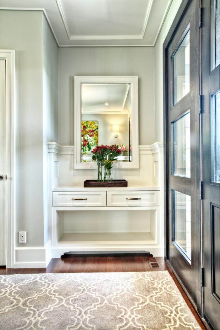 recibidor moderno decorado en tonos claros, bonita decoración con espejo de forma rectangular jarrón con flores