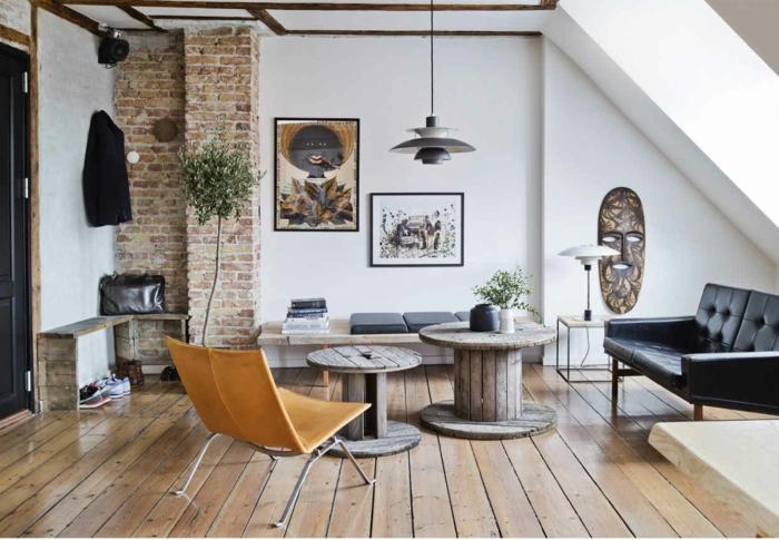 decoracion nordica salon, sala de estar con parte de pared de ladrillo, sofá vintage de cuero negro en capitoné, mesas de cerretel, suelo con tarima, mini recibidor, decoración de pared con motivos precolombinos