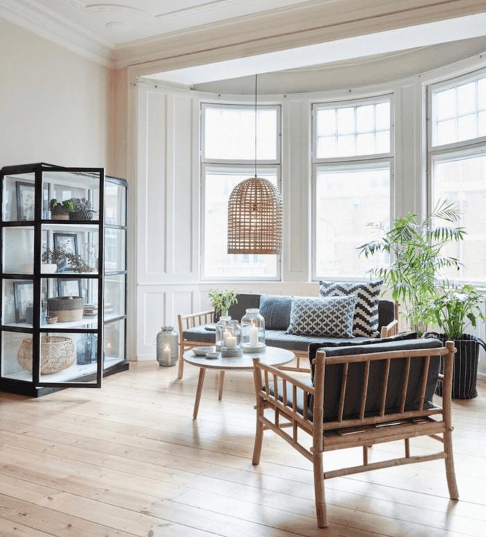 sala de estar con estantería con puertas de vidrio, estilo nórdico, ventanas grandes, sofá y sillón de madera, mesita redonda, portavelas, palmera, suelo con tarima