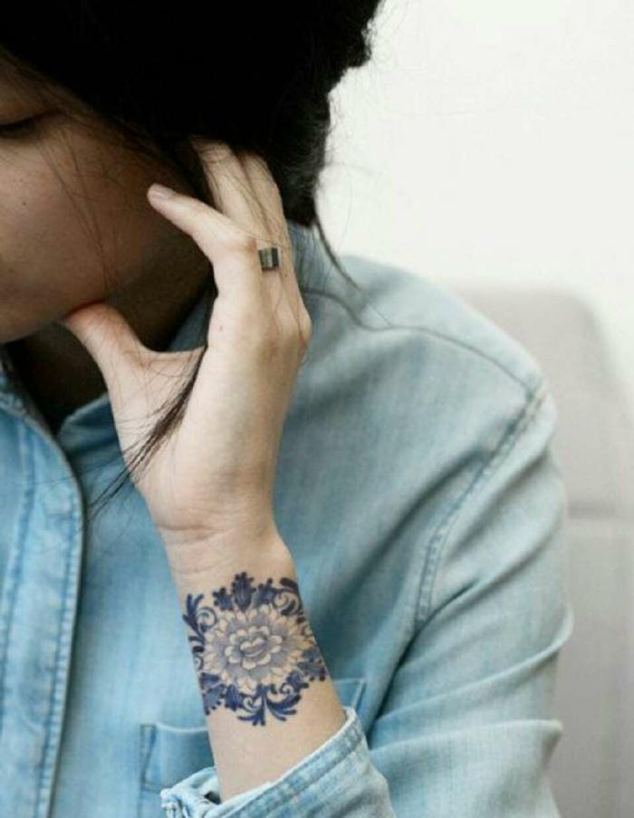mujer con tatuaje brazalete azul en la muñeca con motivos florales, tatuajes pequeños originales, pelo largo recogido, camisa jeans