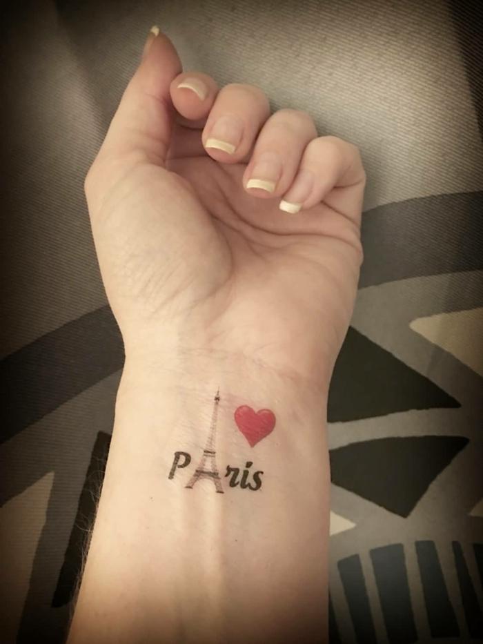 tatuajes muñeca, mano con manicura, tatuaje con el nombre Paris, la torre aifel y corazon rojo, tattoo combinación de imágenes y letras
