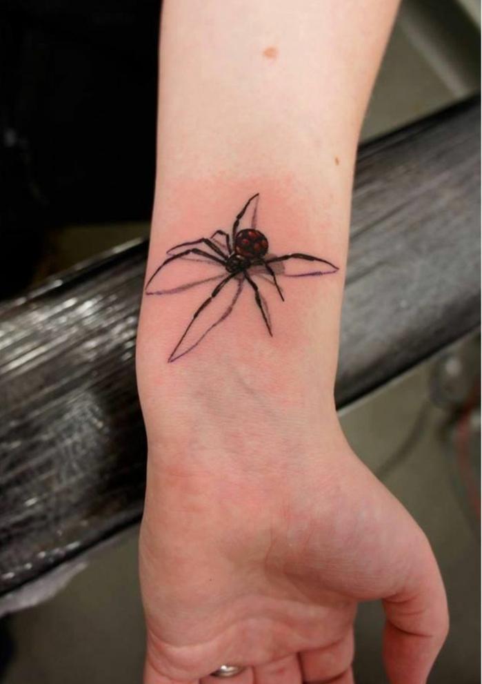 mujer con anillo en el dedo anular, tatuaje de una araña en la muñeca con efecto 3D, tatuajes flechas