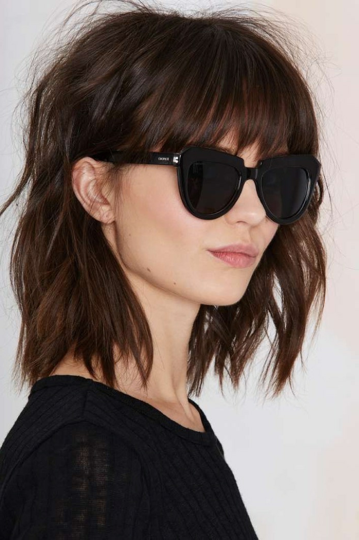 mujer de perfil con gafas de sol negras, media melena con flequillo largo depuntado, cortes de pelo media melena
