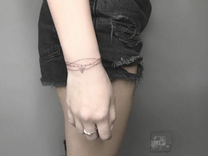 tatuaje femenino como pulsera decorativa, líneas finas. mujer con pantalones cortos y anillo, tatuajes pequeños para mujeres originales