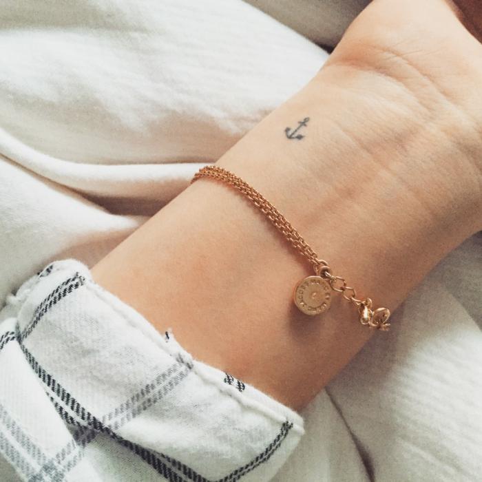 mano de mujer con pulsera en dorado y camisa en cuadrados, tatuajes en la muñeca, mini tatuaje ancla