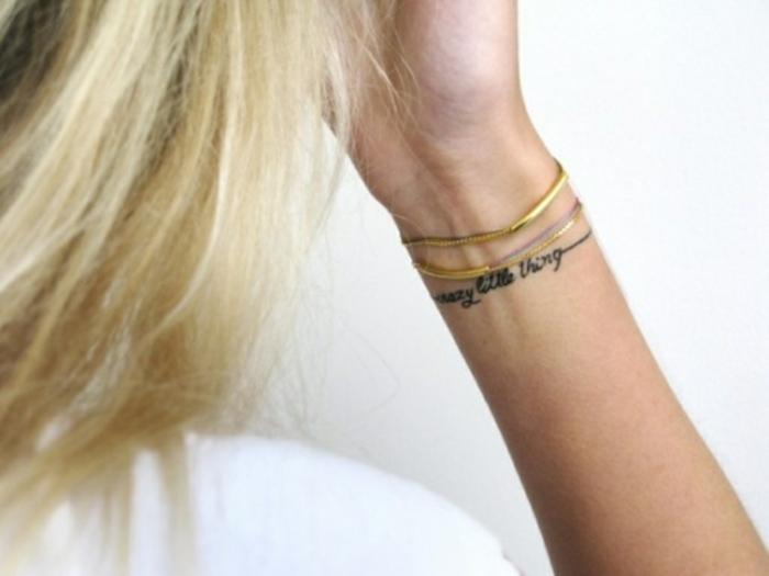 tatuaje femenino con frase en cursiva y brazalete, mujer rubia, con pulseras, tatuajes pequeños para mujeres originales