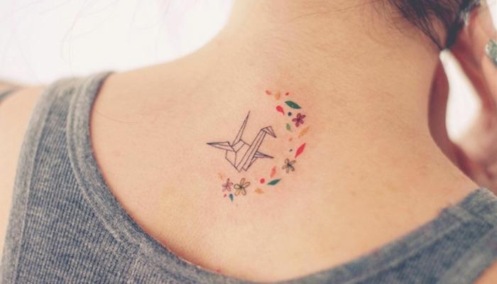 tatuaje de color en la nuca, cisne otigami y hojas de flores, medio circulo, tatuajes elegantes, idea para mujeres