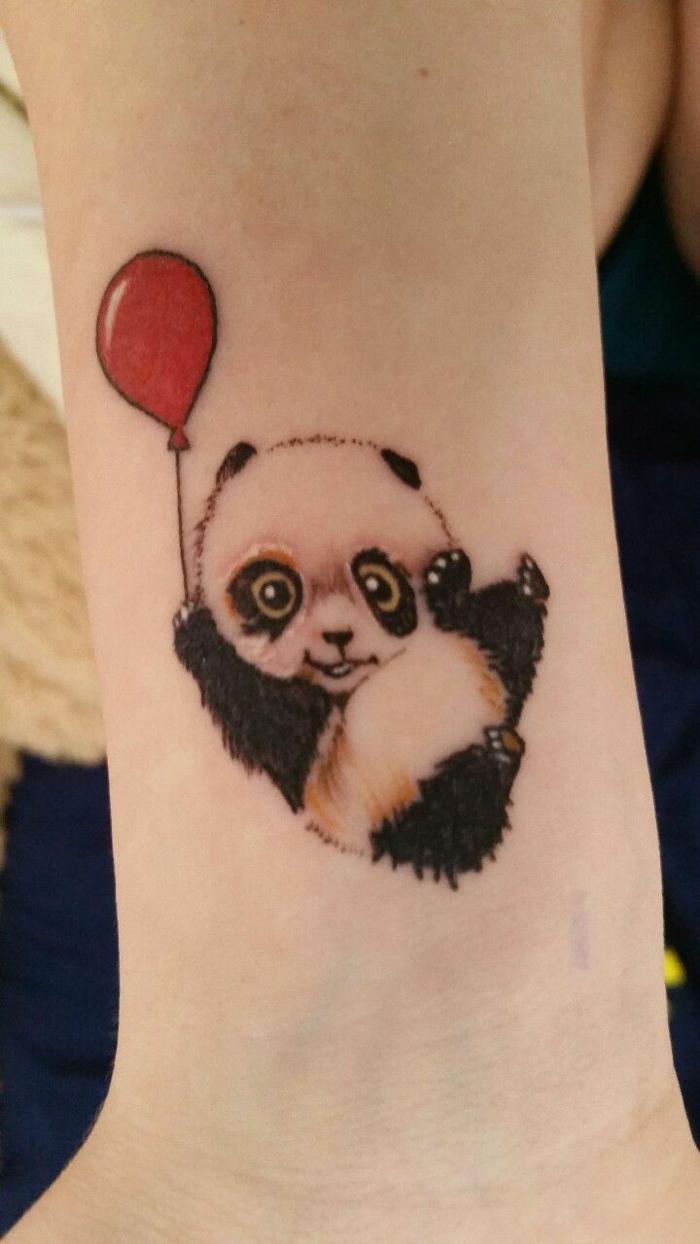 tatuajes en la muñeca, diseño de tatuaje de color para mujeres, panda en blanco y negro con globo rojo