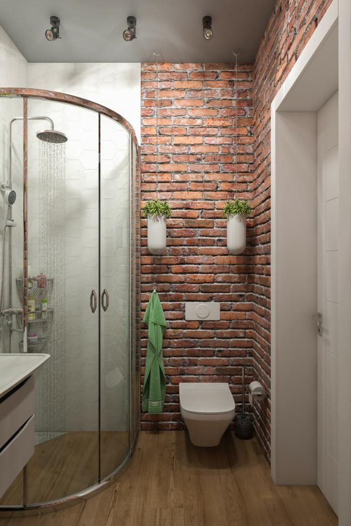 decoracion baños pequeños, pared de ladrillo visto con macetas colgantes blancas, cabina de ducha en el ángulo, suelo de madera, colores contrastes