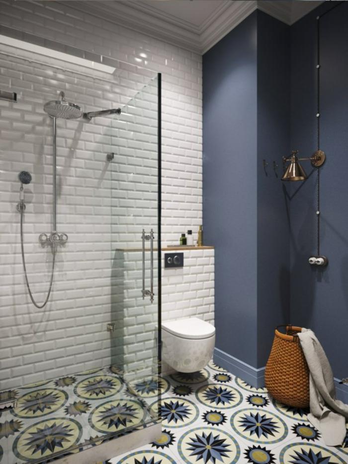 cuartos de baño, baño con paredes en azul y blanco, suelo con baldosas con patron de flores, ducha de obra con mampara de vidrio,