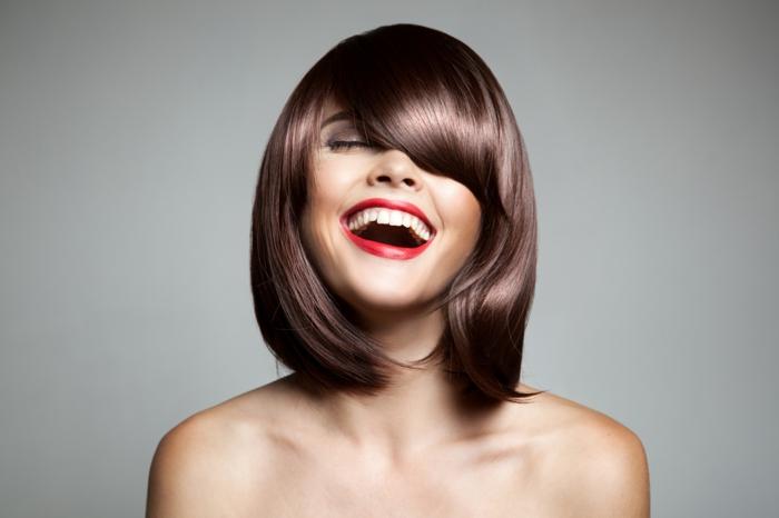foto artística, mujer on pelo corto brillante y labios rojos, peinado con flequillo largo inclinado a un lado, melena con flequillo