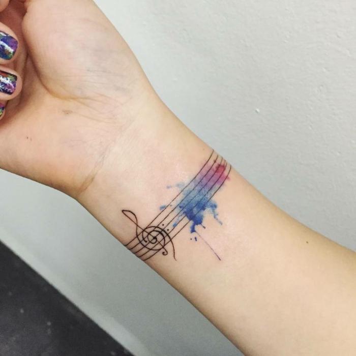 tatuaje para músicos o amantes de la música, mujer con tatuaje en la muñeca, pentagrama con clave sol y manchas efecto acuarela, color morado y azul, tattoo en la muñeca