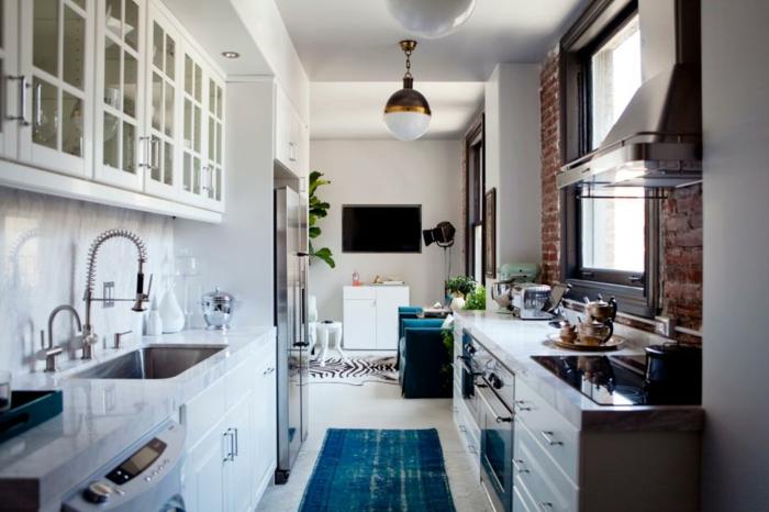 pequeña cocina alargada abierta al salón, armarios y alacenas en blanco, pared revestida de ladrillos y alfombra en color turquesa
