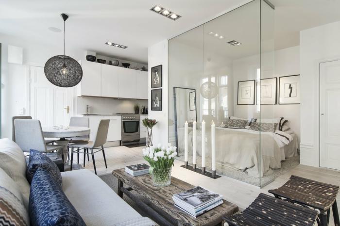 espacio grande, habitación separada con mámpara de vidrio, cama doble, comedor con mesa redonda, mesita baja de madera rustica, sofá y flores, dormitorio nordico