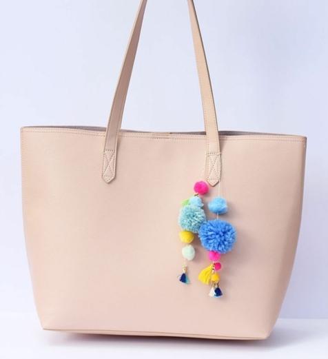 bolso sencillo en color beige decorado con pompones de lana pequeños, cómo hacer pompones de lana turotial completo