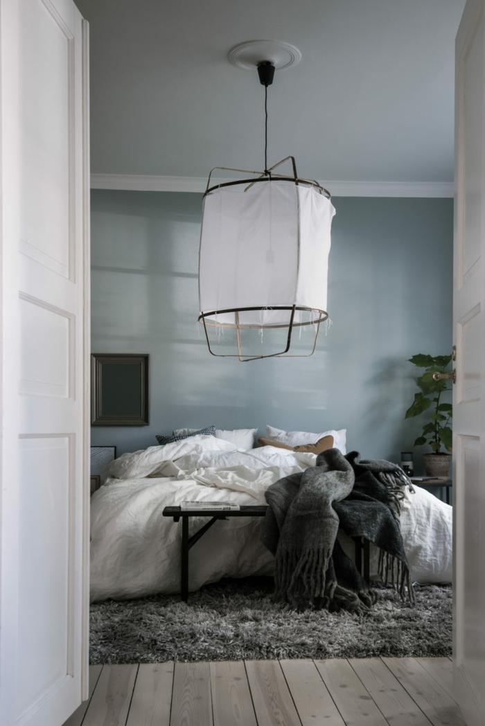 dormitorio minimalista, habitacion gris y blanca, pared en gris azulado, lampara grande colgante, suelo de tarima, tapete peludo