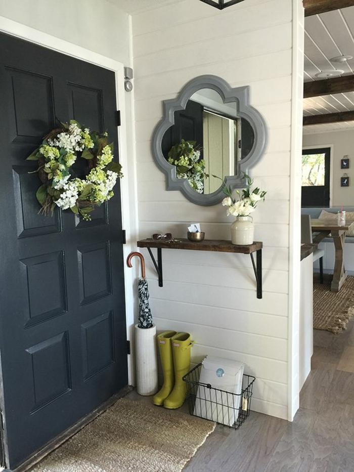 decoración de flores en un recibidor moderno, corona de flores en la pared, paredes en blanco y espejo de marco gris