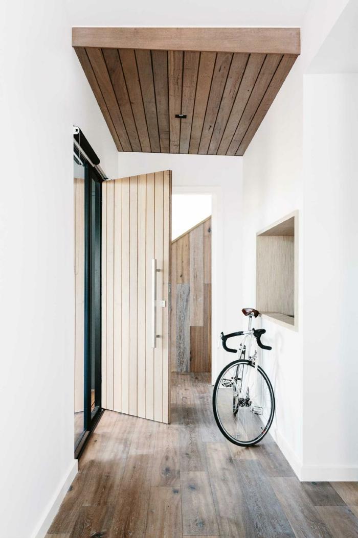 espacio luminoso decorado en blanco, suelo y techo de parquet, recibidor moderno con decoración minimalista