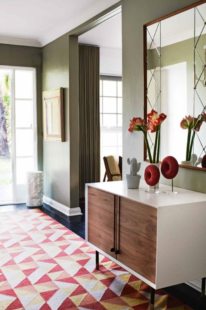 diseño elegante y mdoerno, entraditas modernas con detalles decorativos en rojo, paredes en color ocre y grande espejo