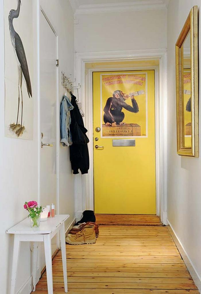 pequeño recibidor decorado de una pintura y grande espejo con marco dorado, muebles de entrada modernos y bonitos