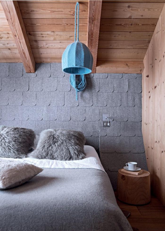 idea decoracion dormitorio rustico, habitación gris, techo inclinado de amdera con vigas, cama doble, pared cubierta de pedazos de tela gris oscuro, lámpara azul colgante