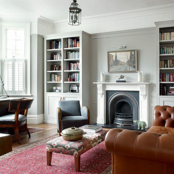 decoracion clásica, salón grande, habitación gris, sofá de cuero, mesa tapizada, alfombra persa, luz natural, chimenea y pintura al oleo, librerías paralelas