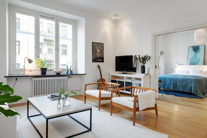 salon nordico, dormitorio matrimonio, suelo laminado, sillas bajas de madera, mesa cuadrada, televisor y guitarra, plantas verdes