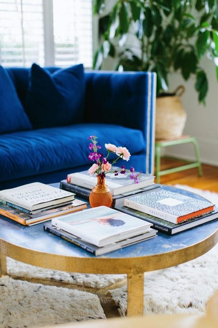 mesa redonda baja con revistas, estilo nórdico, muebles escandinavos, sofá de terciopleo azul, planta verde, alfombra blanca