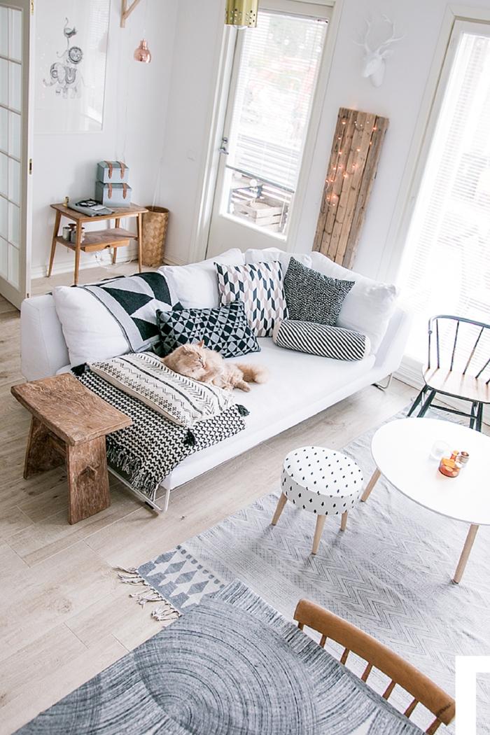 salon luminoso, decoracion en blanco y gris, foto desde arriba, sofá con cojines, mesa redonda de madera, taburete en puntos, tapete