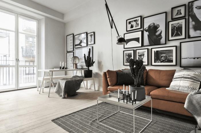 salon con balcon y ventanal, cuadros en blanco y negro, sofá de cuero marrón, cactus, mesa blanca con bancos, suelo de tarima, decoracion nordica,